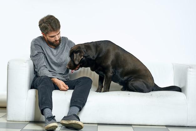 明るい背景の白いソファに黒い犬を連れた男クローズアップクロップドビューペット人間の友人の感情の楽しみ
