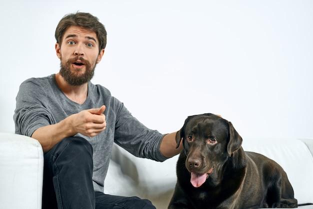明るい空間の白いソファに黒い犬を連れた男クローズアップクロップドビューペットの人間の友人の感情の楽しみ。