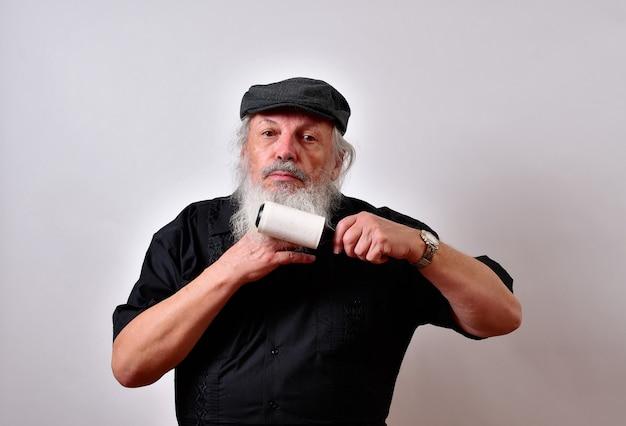 黒い帽子と彼のひげを掃除するシャツを持つ男