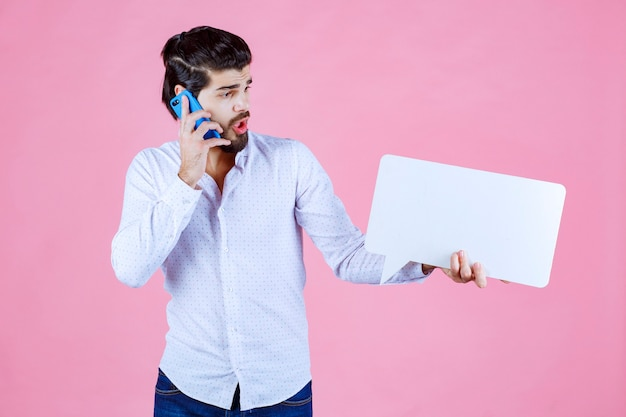電話に話している空白のthinkboardを持つ男と混乱しているように見えます。