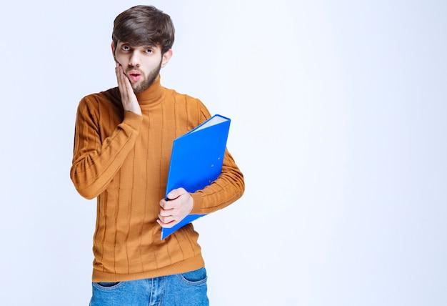 파란색 폴더를 가진 남자는 혼란스럽고 겁에 질려 보입니다.