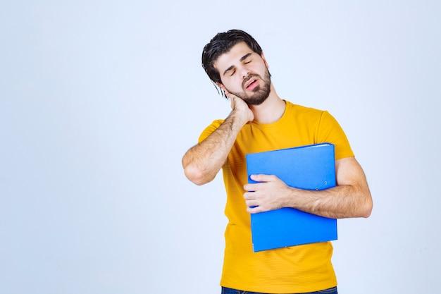 파란색 폴더를 가진 남자는 혼란 스럽거나 경험이 없어 보입니다.