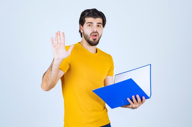青いフォルダーを持つ男は、混乱しているか、経験が浅いように見えます。