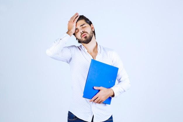 青いフォルダーを持つ男は疲れ果てて不満に見えます