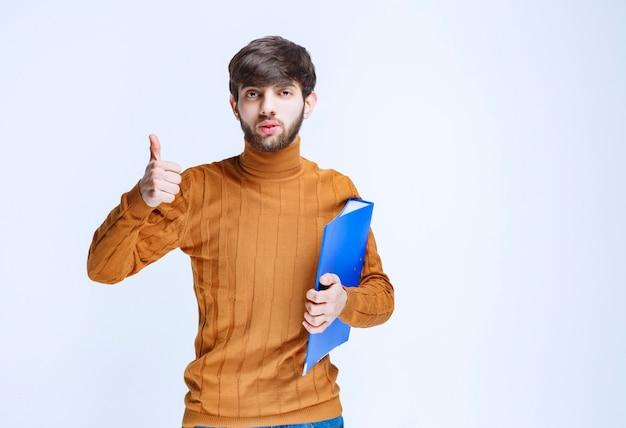 青いフォルダーを持つ男は、力強く満足しているように見えます。