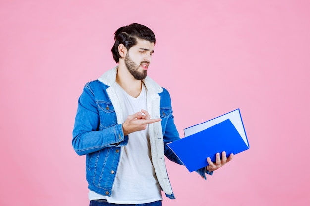 Мужчина с синей папкой выглядит испуганным и усталым