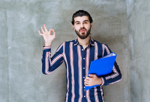 青いフォルダーを持つ男は成功した商取引をしました。