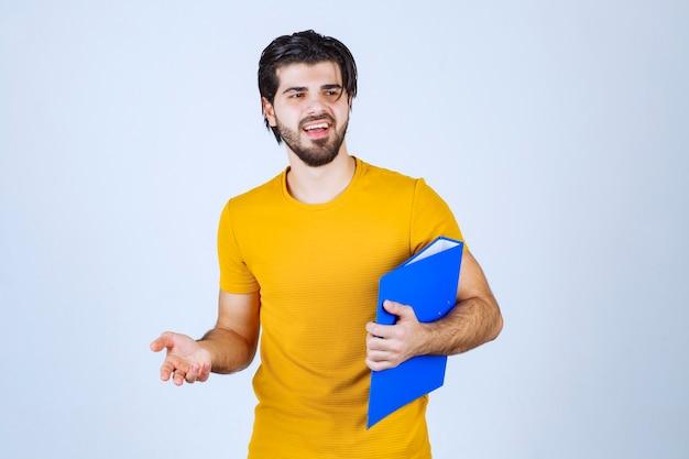 青いフォルダーを持った男が同僚を左側に向け、感情を込めて話している。