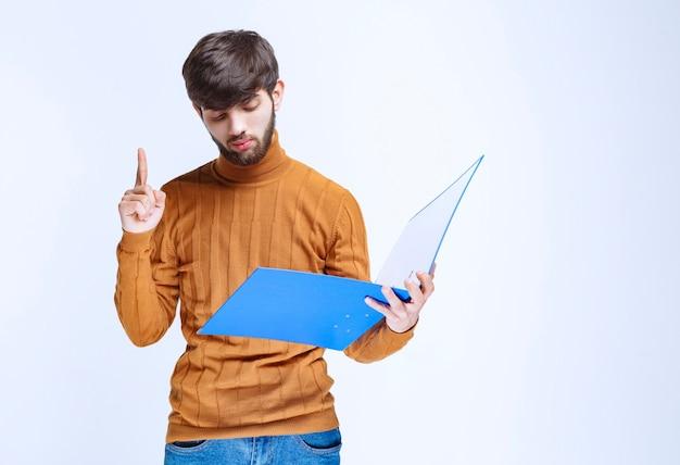 注意のために指を上げる青いフォルダーを持つ男。