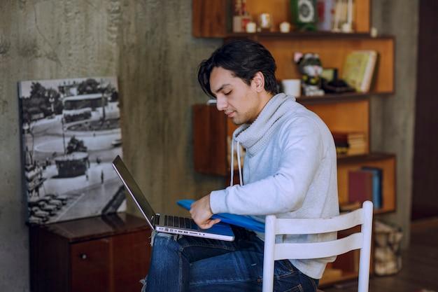 Человек с голубой папкой работает на ноутбуке и выглядит усталым. фото высокого качества