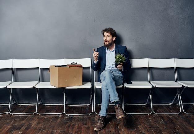 상자를 가진 남자는 물건 문서 해고와 함께 의자에 앉아