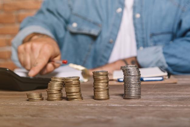 電卓とお金の節約を計算するコインのスタックを持つ男