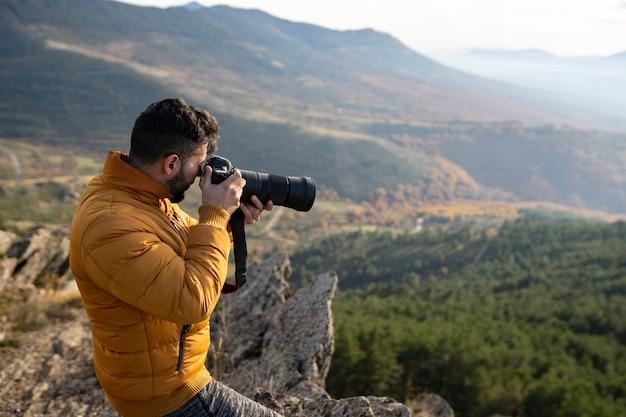 자연 속에서 카메라와 망원 렌즈를 가진 남자