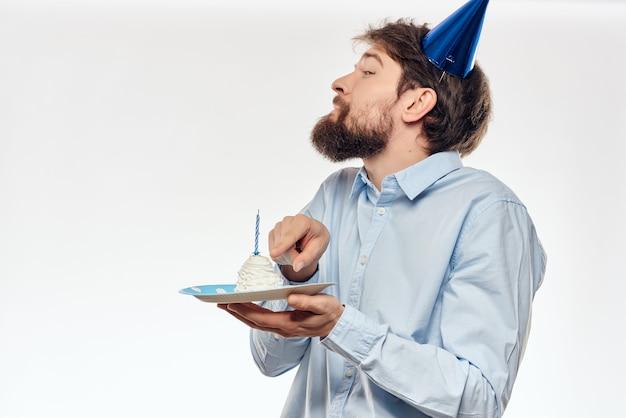 Человек с кепкой на голове тарелка с тортом праздник светлом фоне