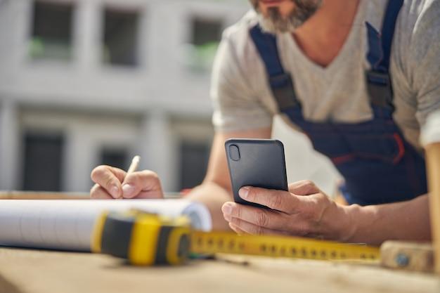 テーブルの上に寄りかかって携帯電話と鉛筆を持つ男