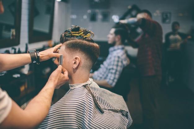 Мужчина с зажимом на голове в парикмахерской