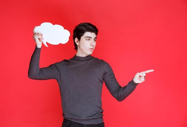 どこかを指している雲の形のthinkboardを持つ男