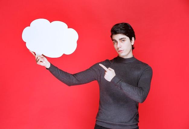 どこかを指している雲の形のthinkboardを持つ男 無料写真