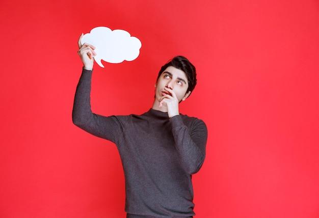 雲の形の思考ボードの思考とブレーンストーミングを持つ男