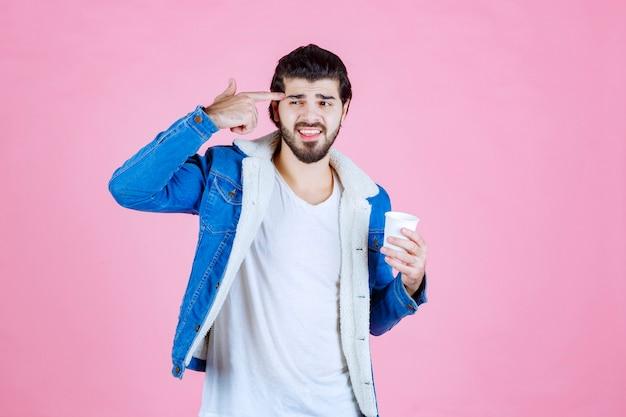 彼の頭を指しているコーヒーカップを持つ男