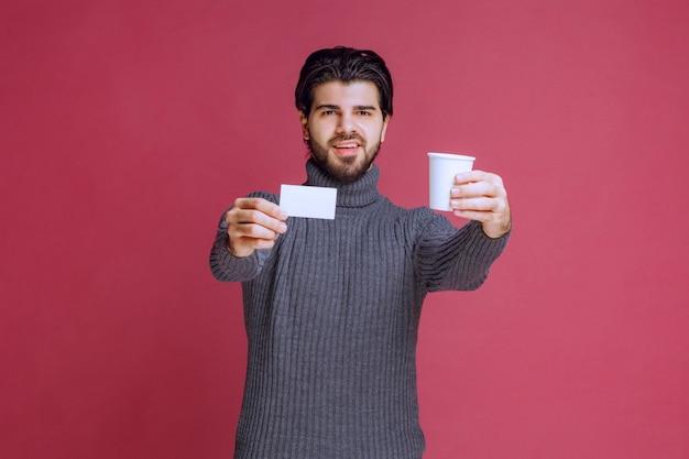彼の請求書または名刺を示すコーヒーカップを持つ男。