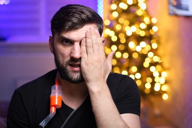 クリスマスライトの背景に肺吸入器のデバイスを持つ男