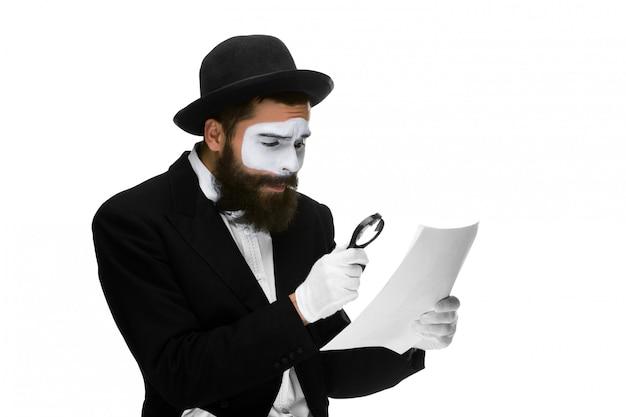 돋보기를 통해 읽고 얼굴 mime 가진 남자