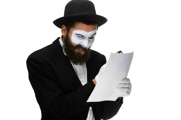 Человек с мимом на лице читает через увеличительное стекло