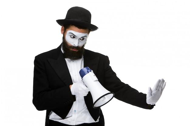 Человек с лицом мима кричит в мегафон