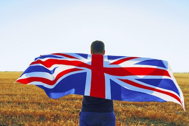Человек с флагом великобритании, стоящий в утреннем поле