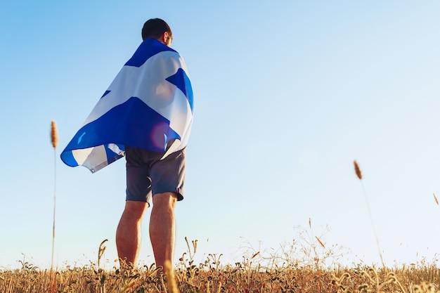 Человек с флагом шотландии, стоящий в утреннем поле
