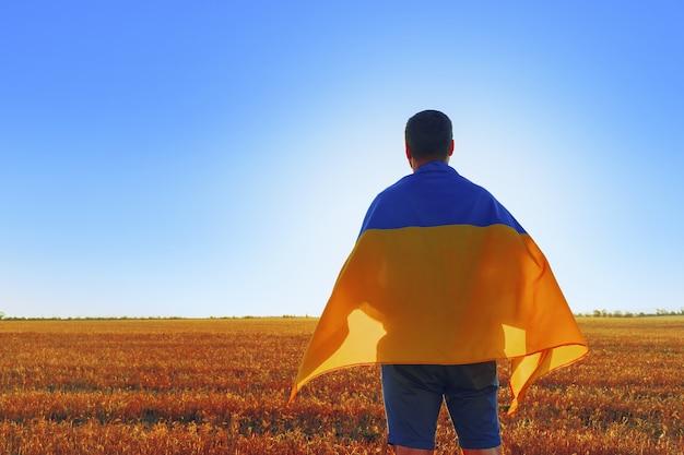 Человек с флагом украины, стоящий в поле