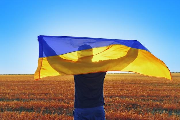 Человек с флагом украины, стоящий в утреннем поле