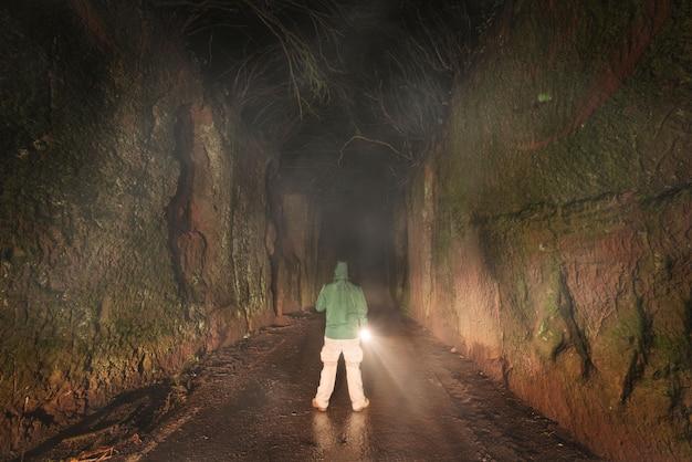 어두운 숲에서 탐험 손전등을 가진 남자