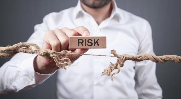木製のブロックにリスクの言葉を示す擦り切れたロープを持つ男。危険