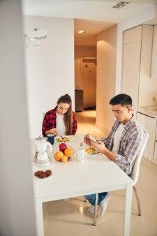가제트를 가진 남자와 그의 아내가 아침을 먹고 있다