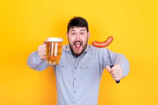 Человек с бокалом пива и жареной колбасой