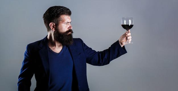 그의 손에 레드 와인 한 잔을 가진 남자. 수염 남자, 수염, 소믈리에 시음 레드 와인. 소믈리에, 와인 한 잔, 와이너리, 남성 와인 메이커.