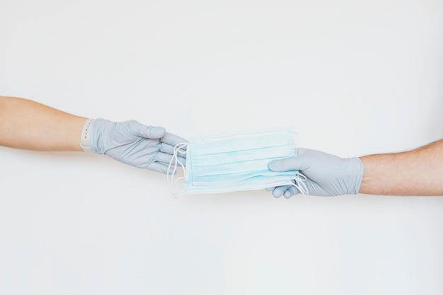 灰色の背景で友人にフェイスマスクを共有する手袋を持つ男