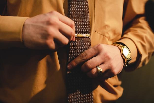 金の腕時計を持つ男はネクタイを調整する