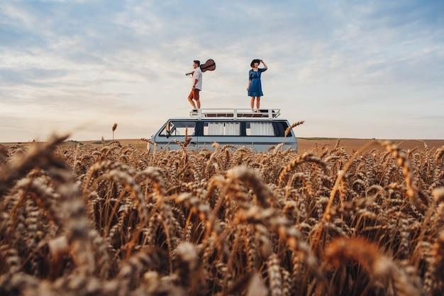 기타를 든 남자와 모자를 쓴 여자가 밀밭의 차 지붕 위에 서 있다.