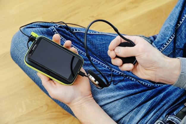 ヘッドフォン、スマートフォン、パワーバンクを持つ男