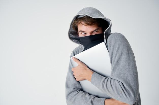 頭巾をかぶった男がノートパソコンの盗難違法侵入犯罪