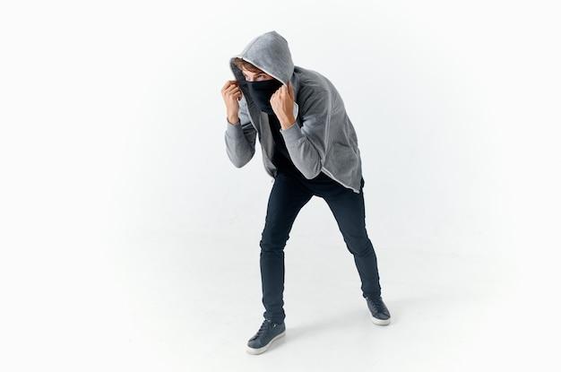 彼の頭の盗難犯罪スタジオの明るい背景にフードを持つ男