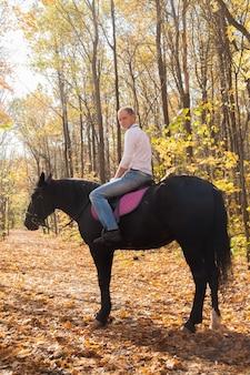가을 숲에서 산책에 말과 함께 남자