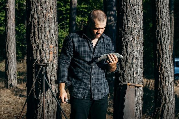 Человек с ножом режет рыбу в лесу