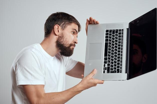 白いtシャツの感情の明るい背景にラップトップを手に持った男明るい背景のトリミングされたビューモデルの肖像画の新技術。