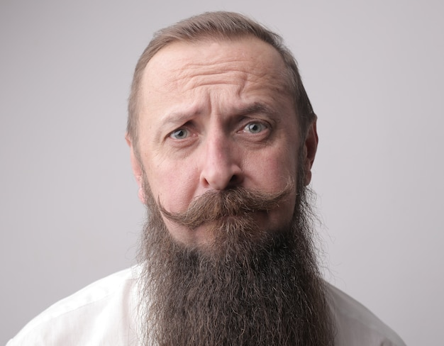 긴 수염과 회색 벽 앞에 서있는 동안 찡그린 콧수염을 가진 남자