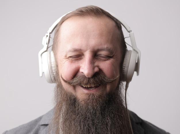灰色の壁の前に立って、白いイヤホンを身に着けている長いあごひげと口ひげを持つ男