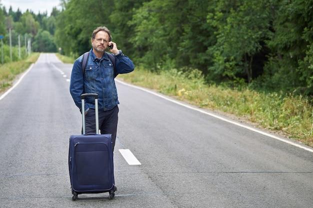 아스팔트 도로 한가운데 서있는 짐을 가진 남자와 휴대 전화에 말한다. 그는 버스를 놓쳤거나 길을 잃었습니다.